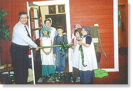 Tom Heffron, left, cut the ribbon Saturday afternoon to open the Dodge County Historical Museum's one-room school project. Assisting Heffron were, front row from left, Caroline Rey, Jared Pullam, Rachel Helgeson, Hannah Giesick; and back row, Diane Hartzheim and Megan Weisensel.